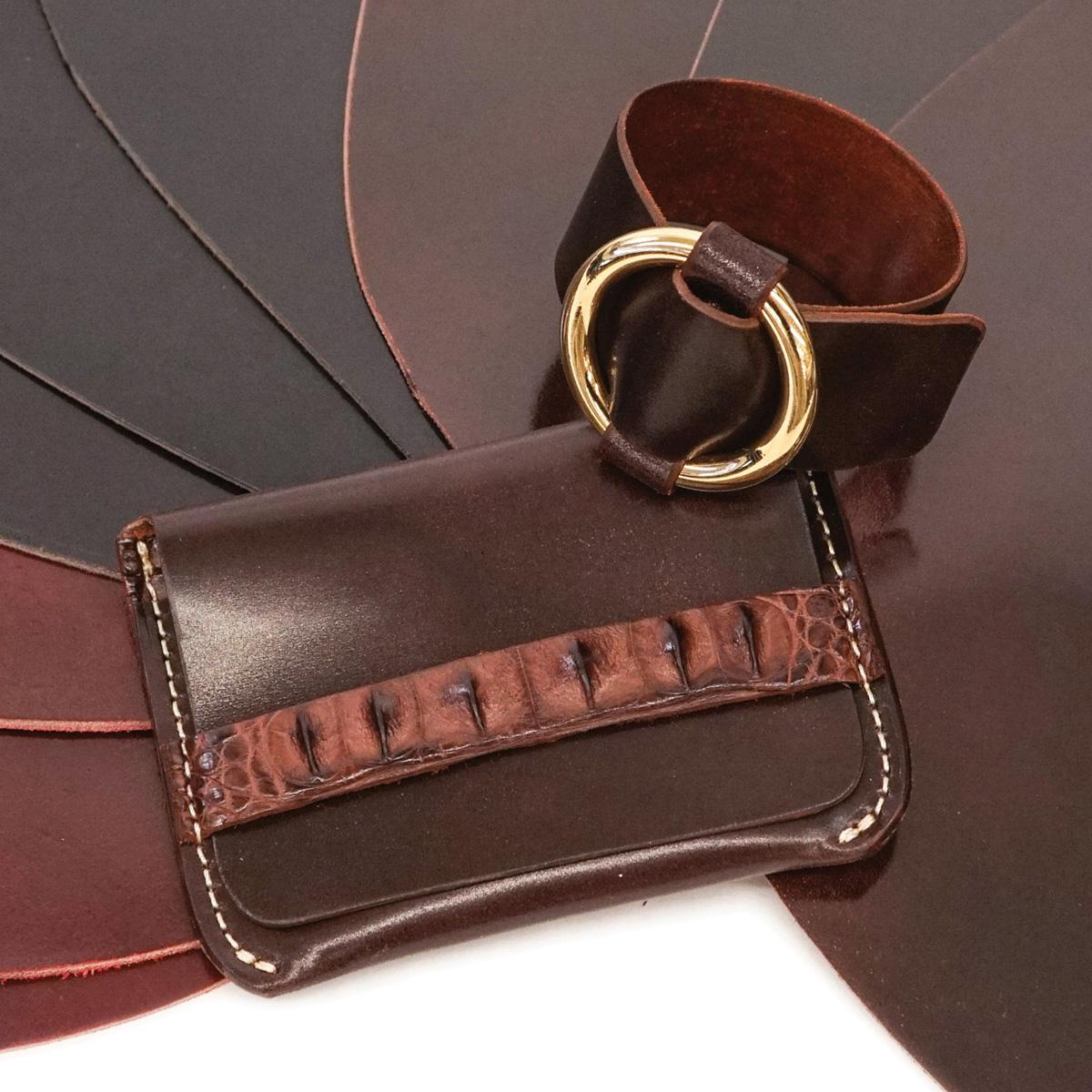 a shell cordovan wallet and cuff sit on top of several shell codorvan pieces in three colors
